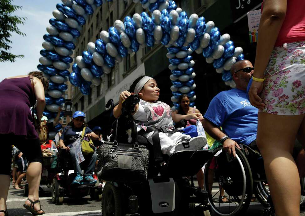 Jessica Lopez, center, participates in the inaugural Disability Pride Parade, Sunday, July 12, 2015, in New York. The parade grand marshal was former U.S. Sen. Tom Harkin, the Iowa Democrat who 25 years ago sponsored the Americans With Disabilities Act. (AP Photo/Seth Wenig) ORG XMIT: NYSW109