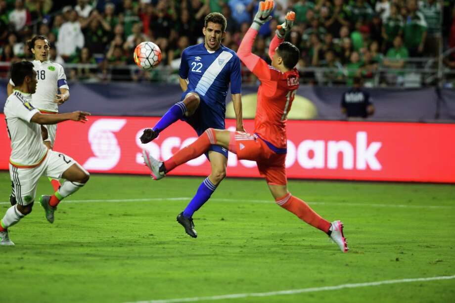 Guatemala National Team's Minor Lopez (L) gets the ball past Mexico National Team goalkeeper Guillermo Ochoa (R) but barely misses the goal during their CONCACAF Gold Cup soccer game at University of Phoenix Stadium July 12, 2015 in Glendale, Arizona. AFP PHOTO/JAROD OPPERMANJAROD OPPERMAN/AFP/Getty Images Photo: JAROD OPPERMAN, Stringer / JAROD OPPERMAN