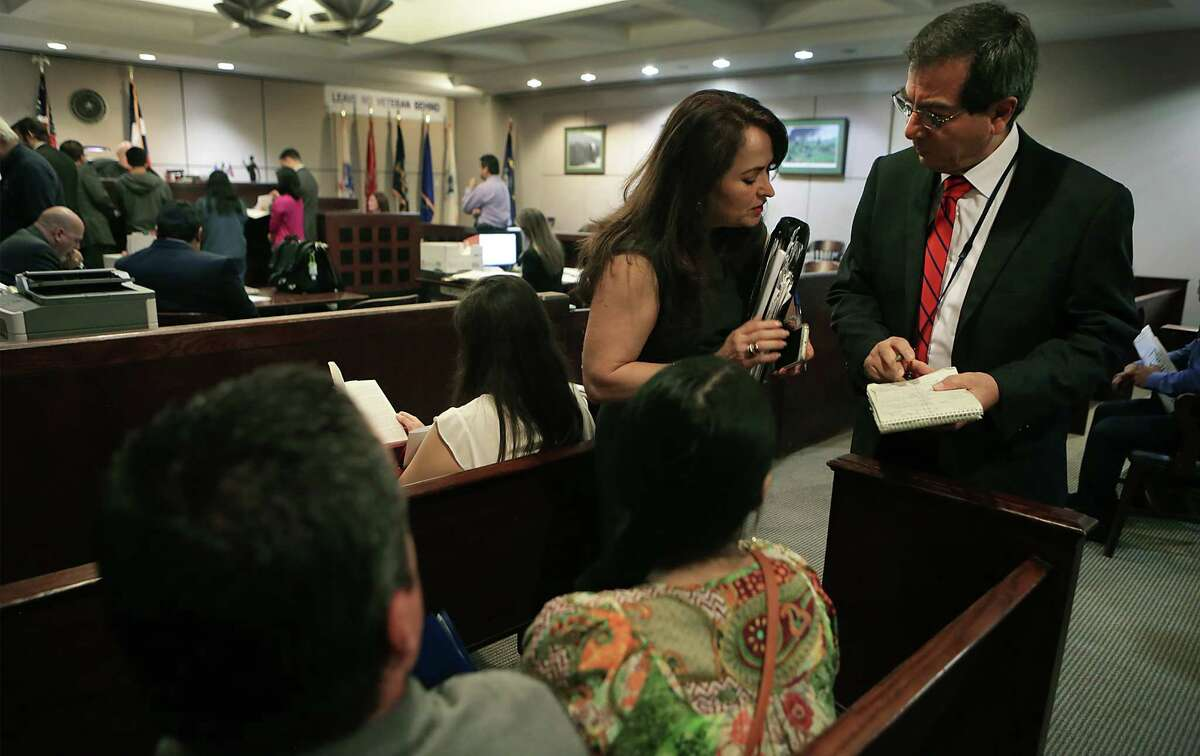 Jorge Valle, right, a Texas State Licensed Court Interpreter at the Bexar County Courthouse, speaks with defense attorney Alma Benavides about her client that doesn't speak english. Valle interpreted for her when the Judge heard her plea on Monday, June 29, 2015.