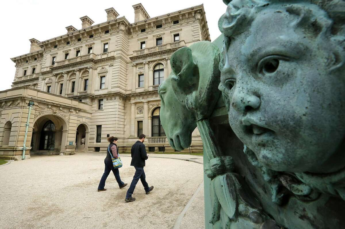 FILE - In this Dec. 1, 2014 file photo, visitors walk past a lamppost sculpture, right, near an entrance to The Breakers mansion, in Newport, R.I. The Vanderbilt family, once synonymous with American wealth and power, has fallen into a full-blown public spat with the organization that now owns their spectacular Rhode Island mansion. (AP Photo/Steven Senne, File)