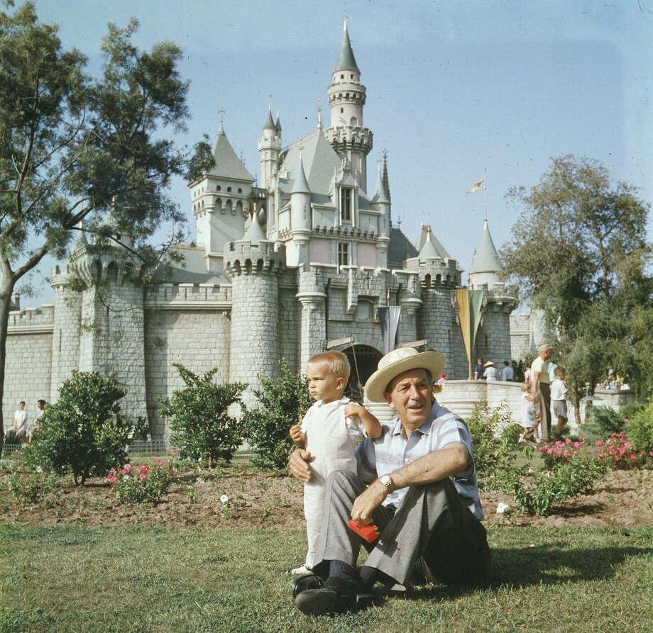 Walt Disney sits on a grassy lawn with his grandson at Disneyland in 1955. Photo: Gene Lester, Getty Images / Archive Photos