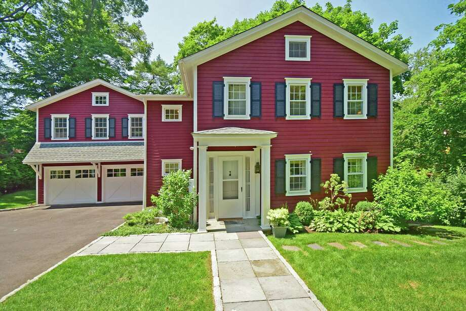 The original siding of this 1856 Colonial was replaced with a rough-cut cedar and painted in a countryside-red hue accented with  black shutters. Photo: Contributed / Contributed Photo / Darien News