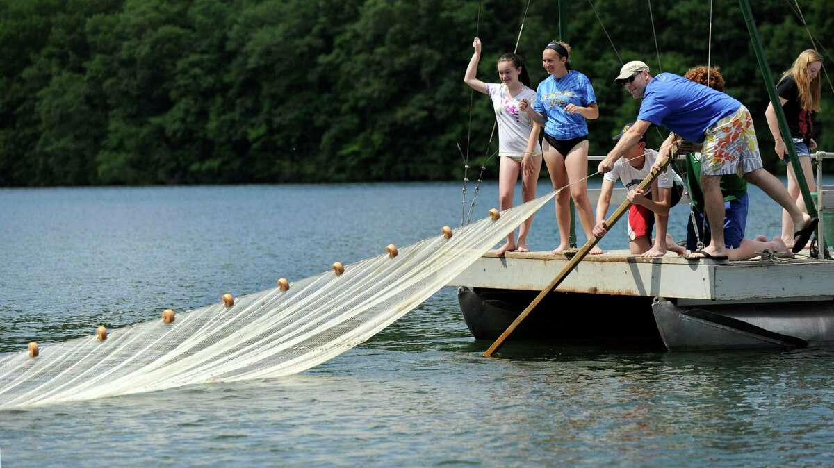 A team casts a net to gather fish samples that will be then to be and evaluated to determine their health and age of the fish. More than 100 local high school students are spending the week conducting research projects on Candlewood Lake. The program is called Project CLEAR. Photo Wednesday, June 24, 2015.