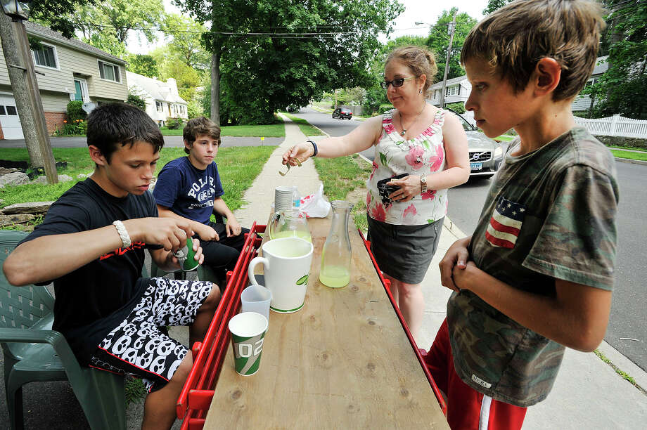 Jack Higgins, left, makes change for Christina Nathanson as Higgins' friends and business partners Nick Palumbo, second from left, and Kristofer Dushi, right, look on at their lemonade stand along Crestview Avenue in Stamford, Conn., on Monday, July 13, 2015. The stand will be open this week from noon to 4 p.m. on Monday, Tuesday, Thursday and Friday. Kristofer is saving money for his mother's birthday, Jack is saving money for a PlayStation 4 and Nick is saving money for a car. Photo: Jason Rearick / Hearst Connecticut Media / Stamford Advocate