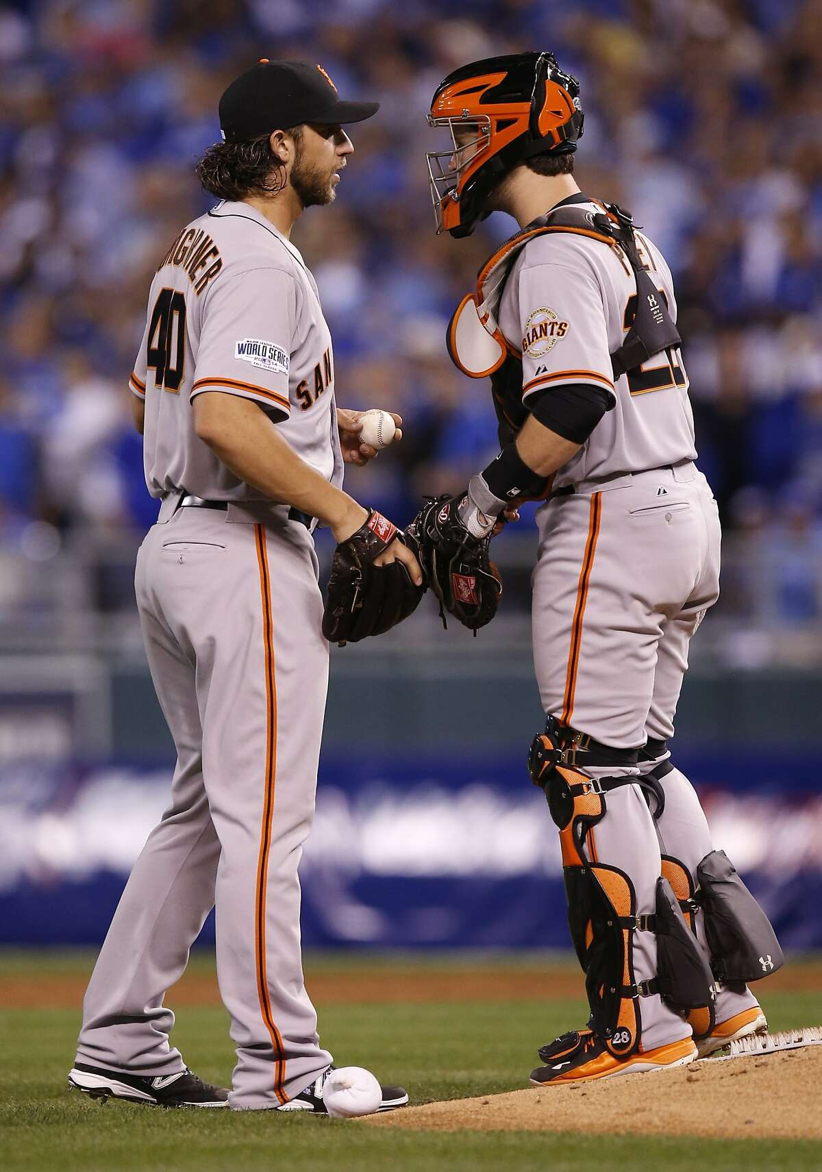 Giants Madison Bumgarner and Buster Posey talk during the second inning in Game 1 of the World Series at Kauffman Stadium on Tuesday, Oct. 21, 2014 in Kansas City, Mo.
