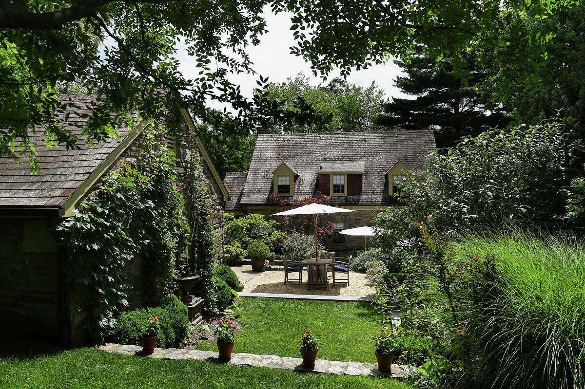 The flagstone terrace behind Rizert's house, outside the kitchen door, is defined by a gently curving low stonewall, creating a casual dining room with table, umbrella, teak chairs and lounges. Illustrates GARDEN-DESIGN (category l), by Audrey Hoffer, special to The Washington Post. Moved Monday, July 13, 2015.