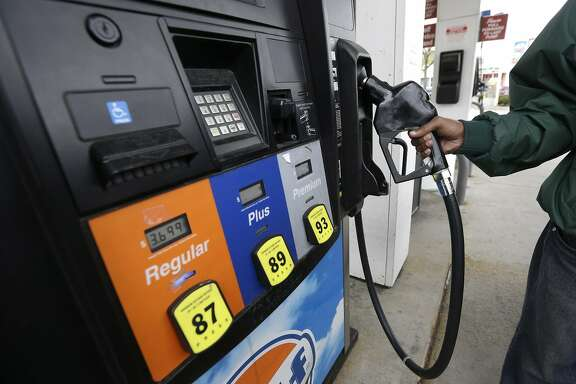 In this Tuesday, April 29. 2014 photo Yosef Wolday fills his car with fuel at a gasoline station, in Brookline, Mass. (AP Photo/Steven Senne)