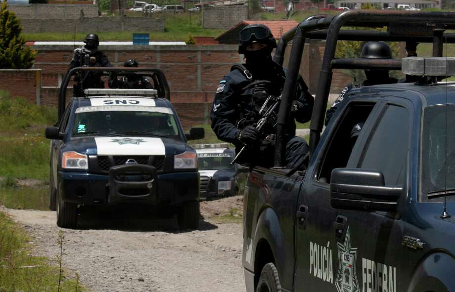 """Federal Police stand guard near a half-built house near the Altiplano maximum security prison in Almoloya, west of Mexico City, Monday, July 13, 2015. A widespread manhunt that included highway checkpoints, stepped up border security and closure of an international airport failed to turn up any trace of Mexican drug kingpin Joaquin """"El Chapo"""" Guzman by Monday, more than 24 hours after he escaped through an underground tunnel leading from his Altiplano prison cell's shower area. (AP Photo/Marco Ugarte) Photo: Marco Ugarte, STR / AP"""