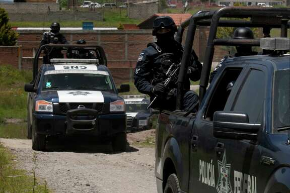 """Federal Police stand guard near a half-built house near the Altiplano maximum security prison in Almoloya, west of Mexico City, Monday, July 13, 2015. A widespread manhunt that included highway checkpoints, stepped up border security and closure of an international airport failed to turn up any trace of Mexican drug kingpin Joaquin """"El Chapo"""" Guzman by Monday, more than 24 hours after he escaped through an underground tunnel leading from his Altiplano prison cell's shower area. (AP Photo/Marco Ugarte)"""