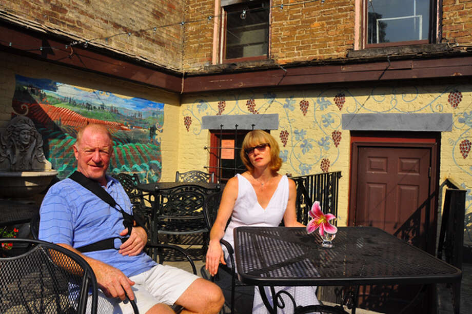 Kevin Everleth is selling the Wine Bar and Bistro on Lark Street in Albany to Silvia Lilly, a school librarian who has worked as a server there a couple of nights a week for the past four and a half years. Above, the two are pictured on the wine bar's back patio.