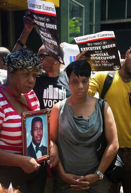 Gwen Carr, left, holding a photo of her son, Eric Garner, stands with Constance Malcolm, right, the mother of police shooting victim Ramarley Graham, at a news conference last week. Photo: Bebeto Matthews, STF / AP