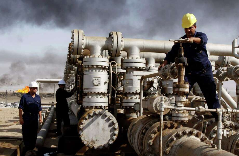 Iraqi laborers work at the Rumaila oil refinery in Zubair near the city of Basra, Iraq.  Photo: Associated Press File Photo / AP