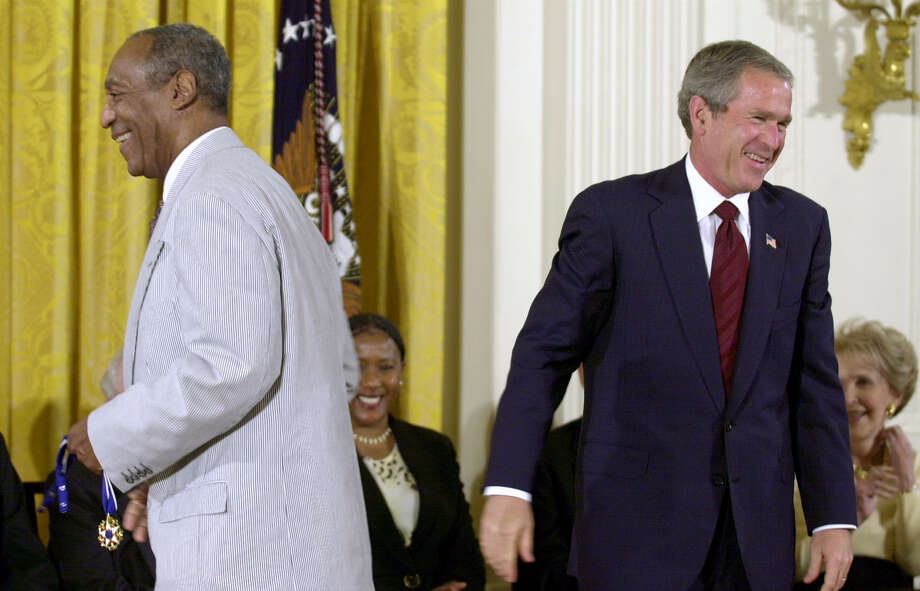 President Bush, right, lets out a laugh after failing to get the clasp together on Bill Cosby's Presidential Medal of Freedom, which Bush tried to put on the entertainer, left, in the East Room of the White House, Tuesday, July 9, 2002, in Washington. Cosby, holding the medal, went back to his seat and immediately put it on himself. (AP Photo/Kenneth Lambert) Photo: KENNETH LAMBERT / AP