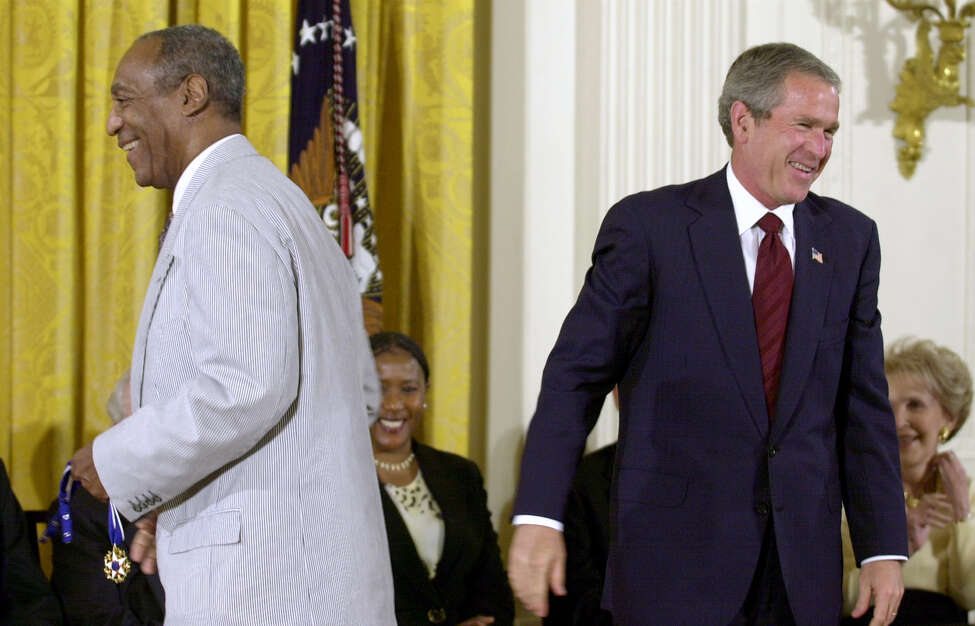 President Bush, right, lets out a laugh after failing to get the clasp together on Bill Cosby's Presidential Medal of Freedom, which Bush tried to put on the entertainer, left, in the East Room of the White House, Tuesday, July 9, 2002, in Washington. Cosby, holding the medal, went back to his seat and immediately put it on himself. (AP Photo/Kenneth Lambert)