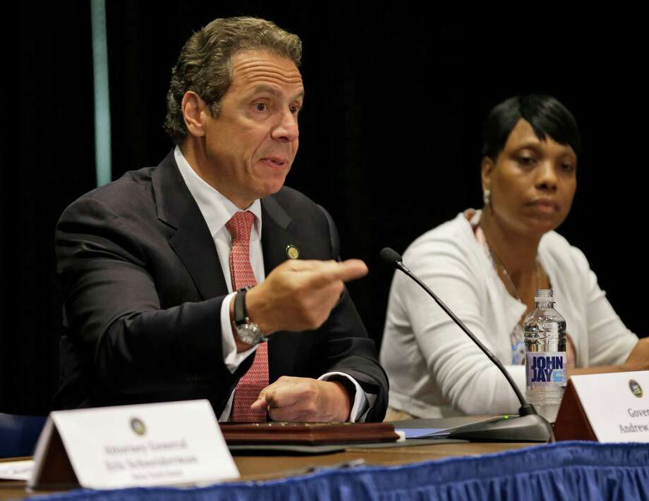 While Constance Malcolm, mother of Ramarley Graham, looks on, New York Gov. Andrew Cuomo speaks during a news conference in New York, Wednesday, July 8, 2015. Cuomo has issued an executive order that puts the office of the state attorney general in charge of investigating killings by police. (AP Photo/Seth Wenig) Photo: Seth Wenig / AP