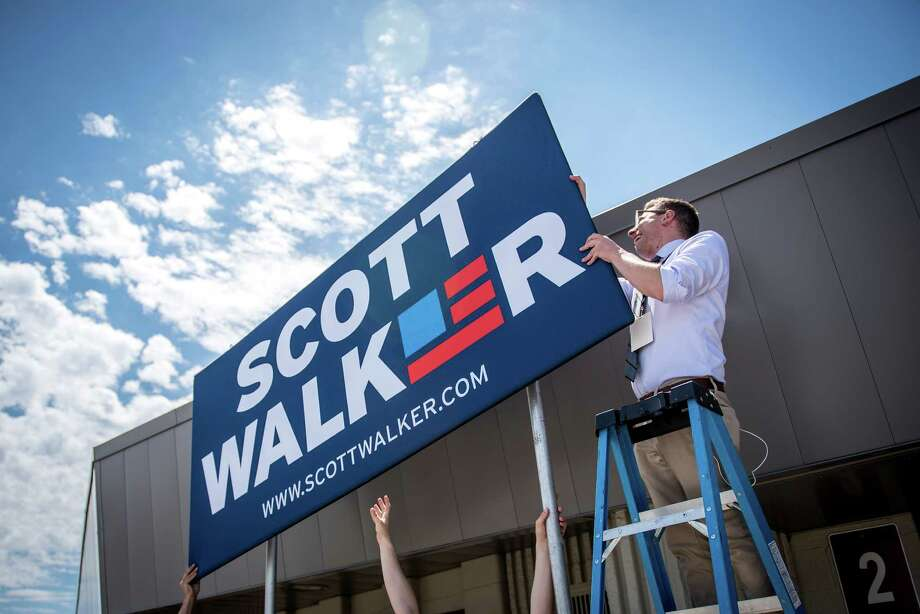 Campaign staff members for Wisconsin Gov. Scott Walker install a sign in front of the Waukesha County Expo Center prior to Walker's announcement Monday that he will seek the 2016 Republican presidential nomination. In his declaration, he cast himself as a Washington outsider who will seek a smaller government. Photo: Christopher Dilts / © 2015 Bloomberg Finance LP