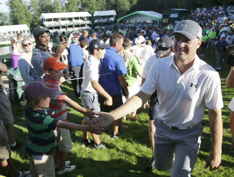 Jordan Spieth, right, celebrates with fans after finishing the third round of the John Deere Classic golf tournament Saturday, July 11, 2015, in Silvis, Ill. (AP Photo/Charles Rex Arbogast) ORG XMIT: ILCA123 Photo: Charles Rex Arbogast / AP