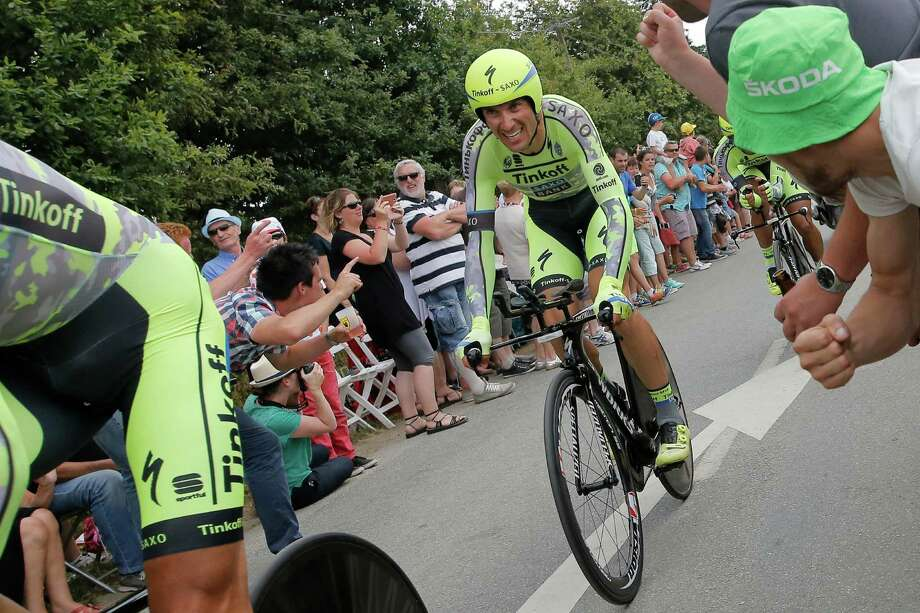 In this Sunday July 12, 2015 image Italy's Ivan Basso, left, trails behind his Tinkoff Saxo team with Spain's Alberto Contador, right, during the ninth stage of the Tour de France cycling race, a team time-trial over 28 kilometers (17.4 miles) with start in Vannes and finish in Plumelec, France. Veteran Basso, a two-time Giro d'Italia winner and once a great rival of Lance Armstrong, has announced that he has cancer in his left testicle and is dropping out of the Tour de France. Basso says he felt pain in his left testicle after a crash in Stage 5 and a medical check later revealed the cancer. (AP Photo/Laurent Cipriani) ORG XMIT: PDJ114 Photo: Laurent Cipriani / AP
