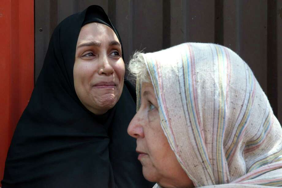 Mary Rezaian, right, mother of detained Washington Post correspondent Jason Rezaian, speaks with journalists as his wife, Yeganeh Salehi, weeps after Monday's hearing. a hearing at the Revolutionary Court in Tehran, Iran, Monday, July 13, 2015. The closed-door trial of detained Rezaian, who has been detained in an Iranian prison for nearly a year, ended Monday after a third session, Iran's official IRNA news agency reported. Rezaian, 39, is being tried in a Revolutionary Court on charges including espionage and distributing propaganda against the Islamic Republic. U.S. officials, the Post and rights groups have criticized his trial and pressed for his release. (AP Photo/Vahid Salemi) Photo: Vahid Salemi, STR / AP