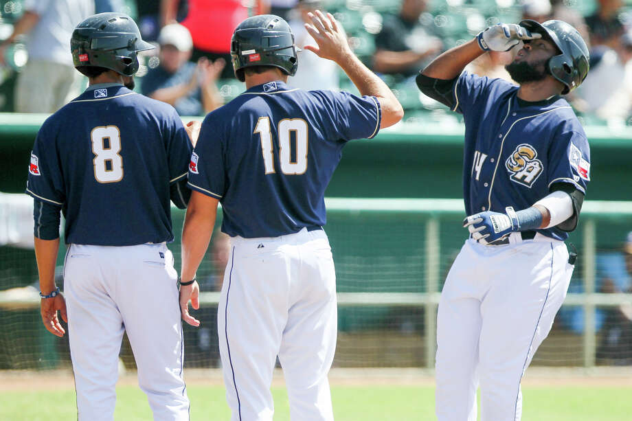 Yeison Asencio of the Missions (from right) is greeted at home plate by Hunter Renfroe and Jose Rondon after hitting a grand slam home run in the first inning of their game with the Tulsa Drillers on Monday, July 13, 2015.Asencio six RBI's after a second home run in the sixth inning to lead the Missions to a 6-5 victory over the Drillers.  MARVIN PFEIFFER/ mpfeiffer@express-news.net Photo: Marvin Pfeiffer, Staff / San Antonio Express-News / Express-News 2015