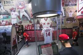 "A visitor browses a display commemorating former Cincinnati Reds player and manager Pete Rose in the ""Kings of the Queen City"" exhibit at the Cincinnati Reds Hall of Fame and Museum, Friday, July 3, 2015, in Cincinnati. Adjacent to the Great American Ball Park, where the July 14 All-Star Game will be played, the Reds' own Hall of Fame and Museum is filled with artifacts and interactive exhibits covering Cincinnati players from the Wrights to the ""Big Red Machine"" of the 1970s to the current team. (AP Photo/John Minchillo)"