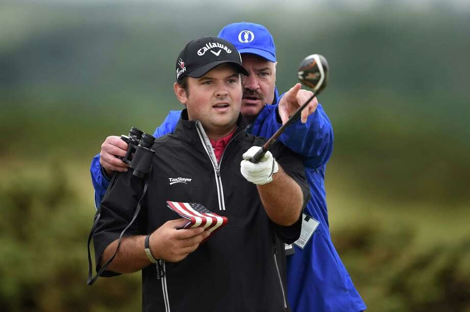 Patrick Reed, who lives in Spring, gets a helping hand from a course marshal during Monday's British Open practice round at St. Andrews, Scotland. Photo: Stuart Franklin, Staff / 2015 Getty Images