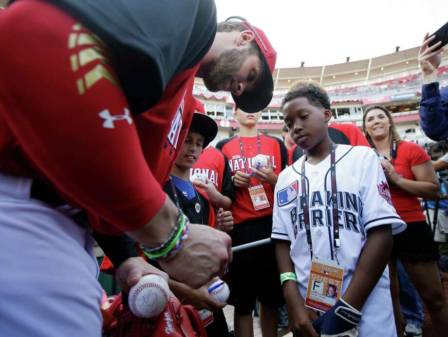 National League's Bryce Harper, of the Washington Nationals, signs autographs for fans during batting practice for the MLB All-Star baseball game, Monday, July 13, 2015, in Cincinnati. (AP Photo/John Minchillo)  ORG XMIT: OHDC140 Photo: John Minchillo / AP