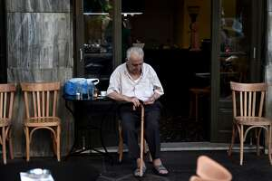 TOPSHOTS An old man sits in a coffee shop in central Athens on July 13, 2015. Greece reached a desperately-needed bailout deal with the eurozone on July 13 after marathon overnight talks, in a historic agreement to prevent the country crashing out of the European single currency. The country's leftist Prime Minister Alexis Tsipras agreed to tough reforms after 17 hours of gruelling negotiations in return for a three-year bailout worth up to 86 billion euros ($96 billion), Greece's third rescue programme in five years. AFP PHOTO / ARIS MESSINISARIS MESSINIS/AFP/Getty Images