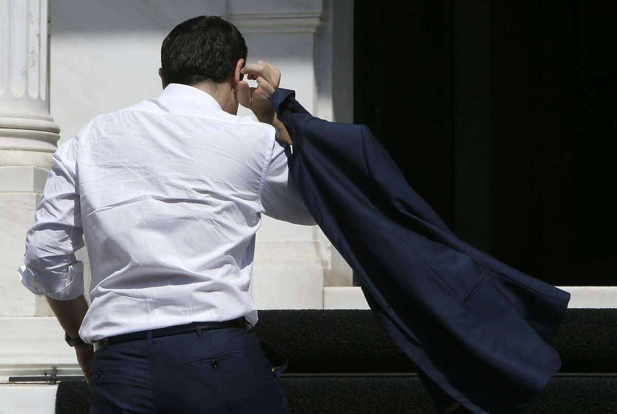 Greece's Prime Minister Alexis Tsipras arrives at his office at Maximos Mansion in Athens, Monday, July 13, 2015. After months of acrimony, Greece finally clinched a bailout agreement with its European creditors on Monday that will, if implemented, secure the country's place in the euro and avoid financial collapse. (AP Photo/Petros Karadjias)
