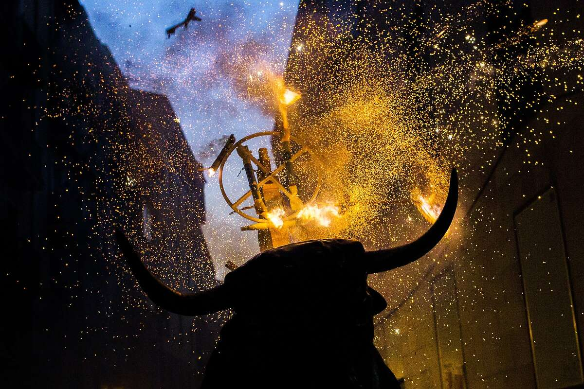"""A flaming fake bull known as a """"Toro de fuego"""" runs after revelers during San Fermin festival in Pamplona, Spain, Monday, July 13, 2015. Revelers from around the world arrive in Pamplona every year to take part in some of the eight days of the running of the bulls. (AP Photo/Andres Kudacki)"""