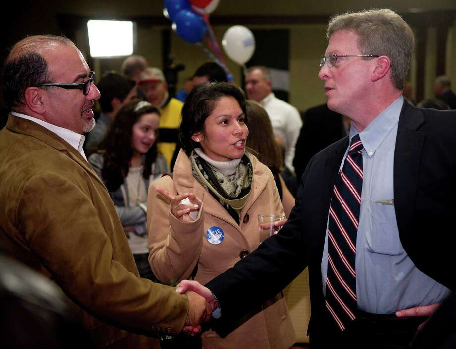 Board of Education member John Leydon, Jr., right, is shown here greeting supporters the night of his re-election to the board in 2013. Photo: Lindsay Perry / Lindsay Perry / Stamford Advocate