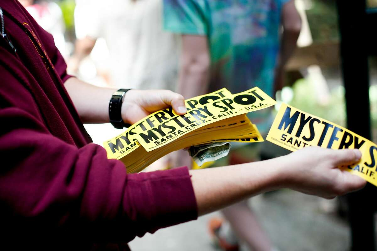 Robbie Oberto gives out bumper stickers after a tour of the Mystery Spot in Santa Cruz, Calif., on Thursday, July 2, 2015.