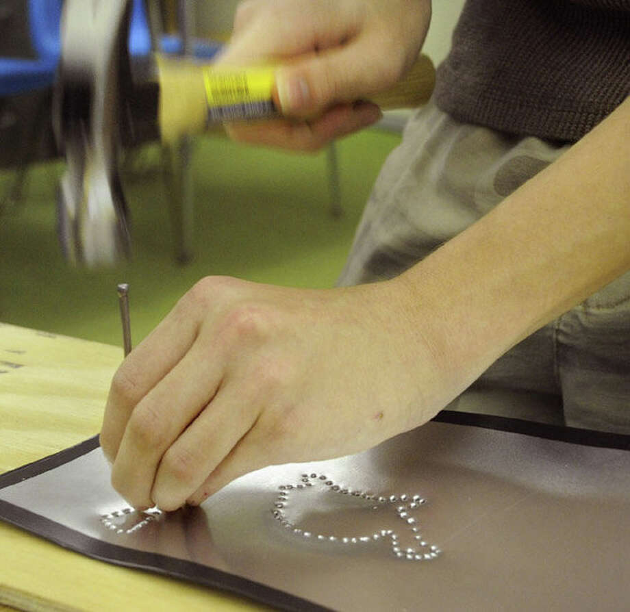 The Wilton Historical Society offers Colonial crafts for children. Above, tin punching is demonstrated. Photo: Contributed Photo / Connecticut Post Contributed