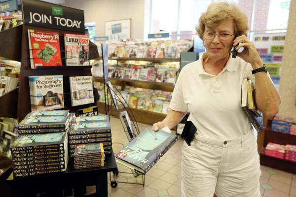 "Julie Bynum, 63, purchases two hard copies and an audiobook of Harper Lee's long-anticipated second novel, ""Go Set a Watchman,"" at the local Barnes & Noble while taking phone book orders from friends on Tuesday, July 14, 2015, in Houston. The book is actually an early version of ""To Kill a Mockingbird"" that was rejected by Lee's publishers. ""Go Set a Watchman"" depicts an adult Scout Finch; when the manuscript was first submitted in the late 1950s, Lee's editors advised her to rewrite the book and focus on a younger Scout. That's how ""To Kill a Mockingbird"" was born. ""Watchman,"" recently discovered in a safety deposit box by Lee's lawyer, is the most pre-ordered print title on Amazon.com since 2007's ""Harry Potter and the Deathly Hallows."""