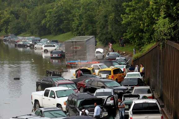 Floodwaters stranded motorists on I-45 near North Main on May 26. Area auto sales in June were up from a year earlier.