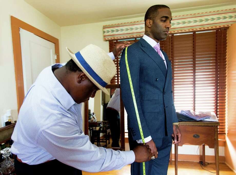 Marcus Andrews, left, has a final fitting with customer and former Broncos star Lenny Walls. Walls is among the A-List clients for Andrews' custom-made menswear that includes Emmett Smith and Antonio Daniels. Photo: William Luther /San Antonio Express-News / © 2015 San Antonio Express-News