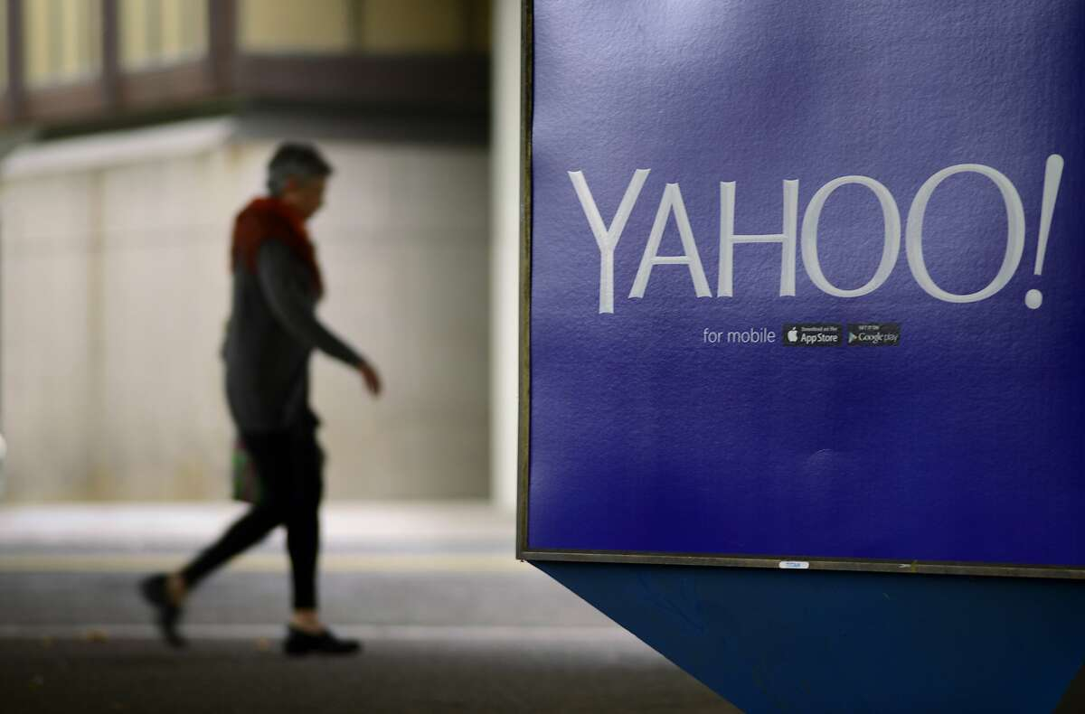 A pedestrian walks under the Rockridge BART Station passing a Yahoo ad in Oakland, California, on Tuesday, July 14, 2015.