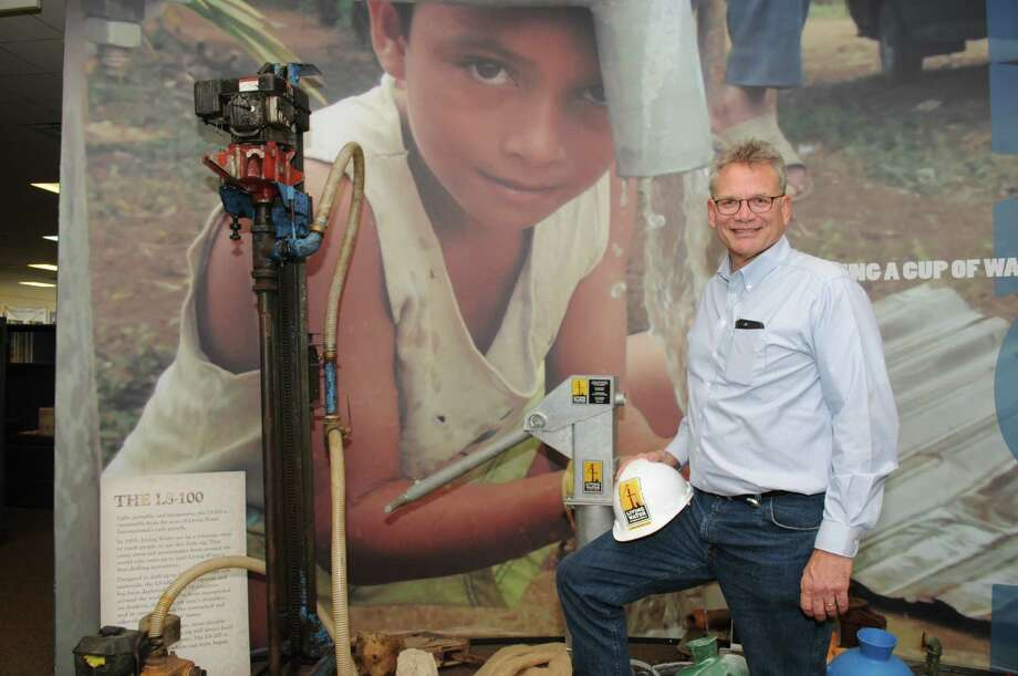 Michael J. Mantel is president/CEO of the Stafford-based Living Water International, a nonprofit that works to bring potable water to poor countries worldwide. He stands next to a sample water well inside the company's office.  Photo: George Wong / Freelance