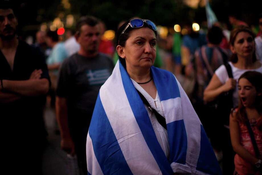 Demonstrators gather near the Greek Parliament during a rally against the government's agreement with its creditors in Athens, in central Athens, Tuesday, July 14, 2015. The eurozone's top official says it's not easy to find a way to get Greece a short-term cash infusion that will help it meet upcoming debt repayments. (AP Photo/Emilio Morenatti) Photo: Emilio Morenatti, STF / AP