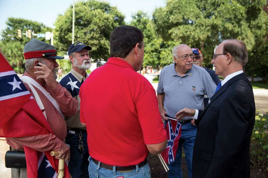 Bexar County Judge Nelson Wolff speaks to Bill Manuel, left, William Smith, second from the left, and other supporters of the Confederate battle flag during a rededication ceremony for the Bexar County Courthouse after the removal of the 1963 and 1970 Gondeck additions in San Antonio, Texas on July 14, 2015. The renovation restored the Bexar County Courthouse back to its original historic faade. Photo: Carolyn Van Houten, Staff / San Antonio Express-News / 2015 San Antonio Express-News