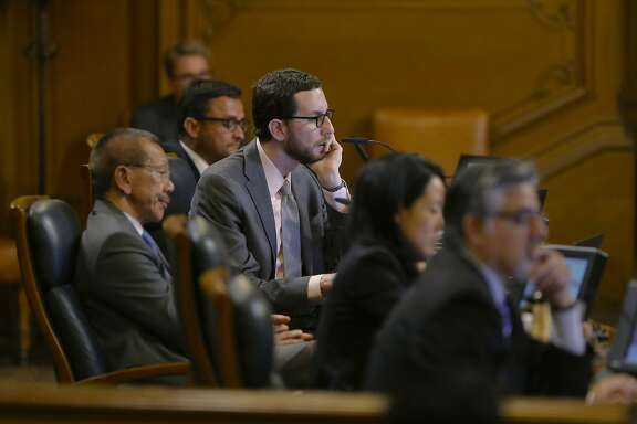 Supervisors, Scott Wiener, (center) listen to comments as the San Francisco Board of Supervisor prepare to vote on competing measures to regulate Airbnb and other short-term rental services in  San Francisco, Calif., on Tues. July 14, 2015.