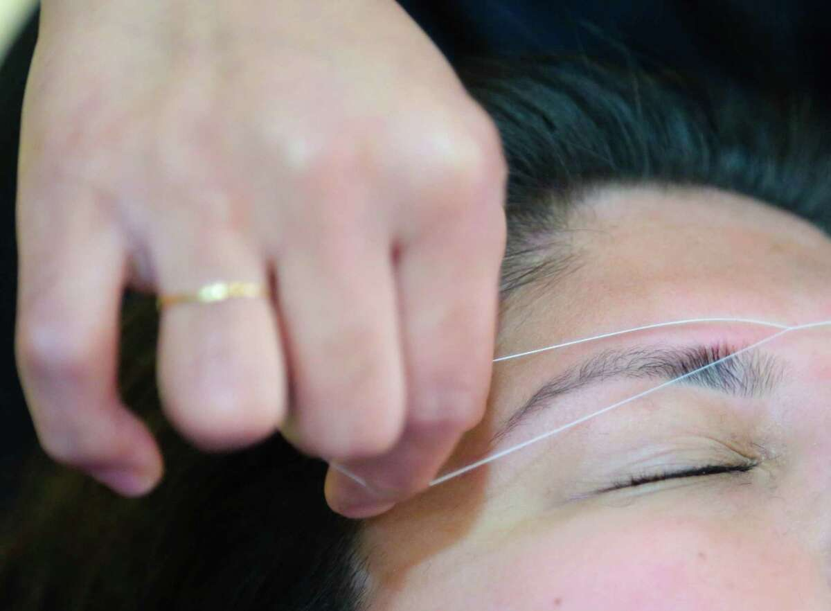 A customer has her eye brows threaded by Manisha Gelal at Perfect Browz Tuesday July 14, 2015. Perfect Browz is a business located inside HEB on Blackhawk Blvd. in Houston, Texas. (Billy Smith II / Houston Chronicle)