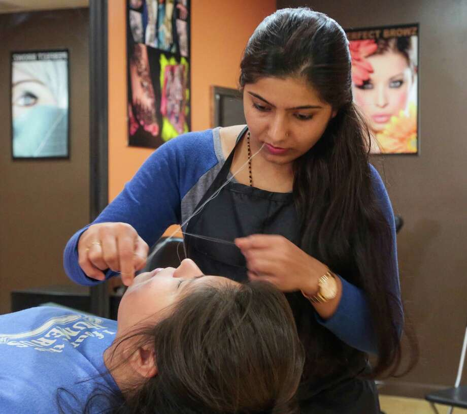 A customer has her eye brows threaded by Manisha Gelal   at Perfect Browz Tuesday July 14, 2015. Perfect Browz is a business located inside HEB on Blackhawk Blvd. in Houston, Texas. (Billy Smith II / Houston Chronicle) Photo: Billy Smith II, Staff / © 2015 Houston Chronicle
