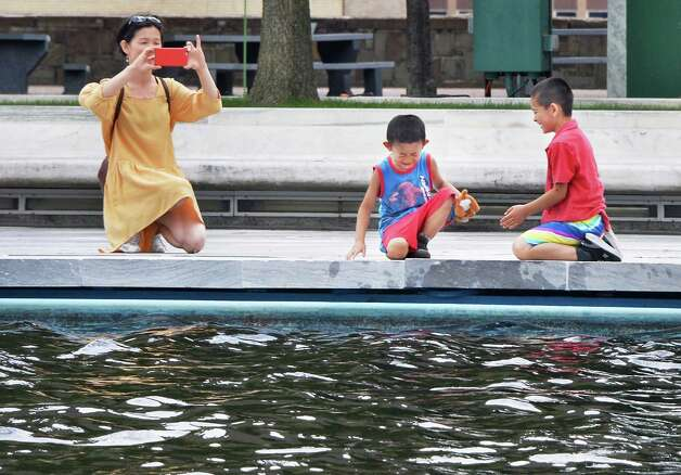 Vivian Cai of Quebec City photographs her sons Oliver, 5, and Victor, 7, right, at the reflecting pool on the Empire State Plaza Tuesday July 14, 2015 in Albany, NY.  (John  Carl D'Annibale / Times Union) Photo: John Carl D'Annibale / 00032601A
