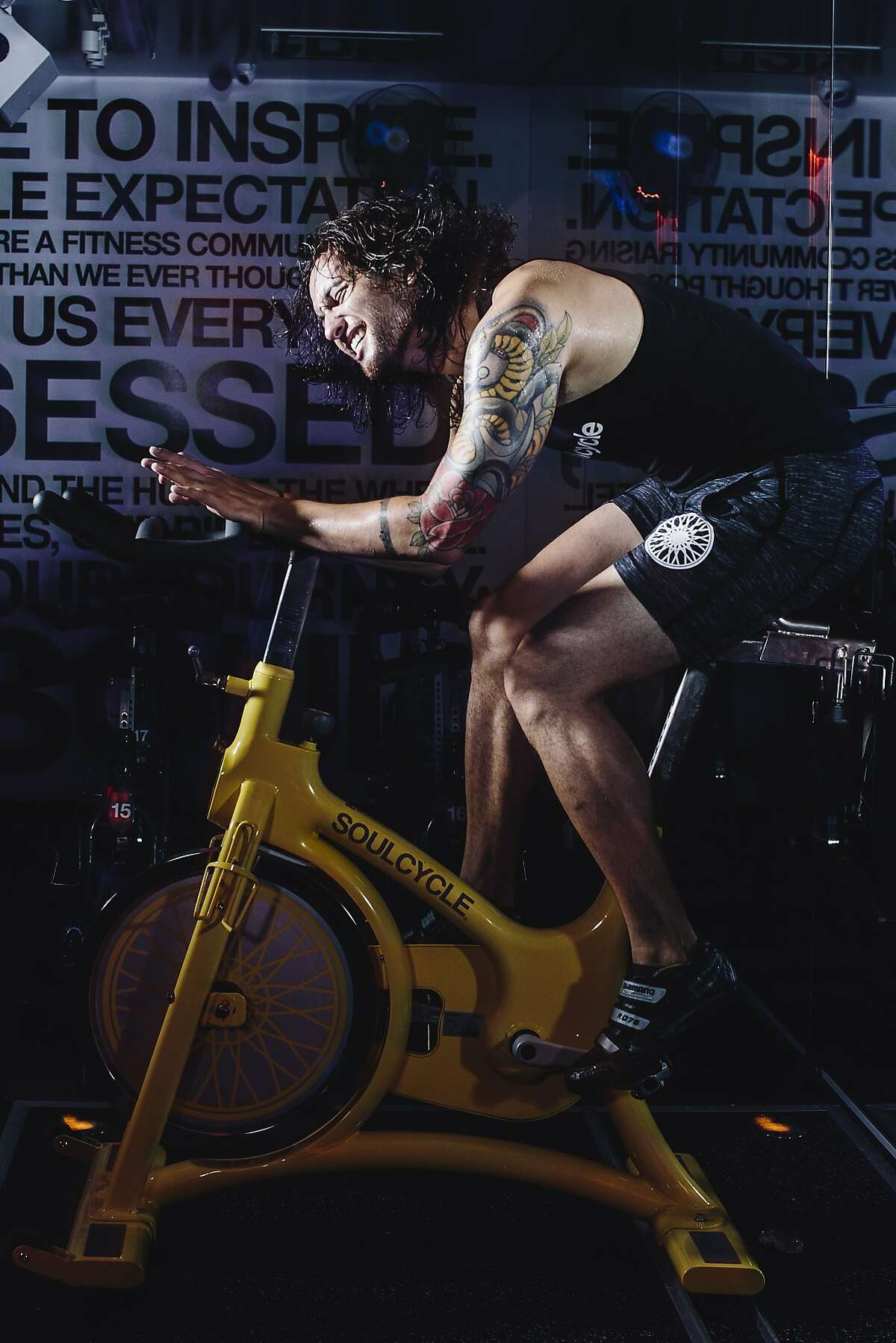 Ian McAndrews, a SoulCycle instructor, spins on a stationary bike at the company's new Castro location in San Francisco, Calif. on Friday, July 10, 2015.
