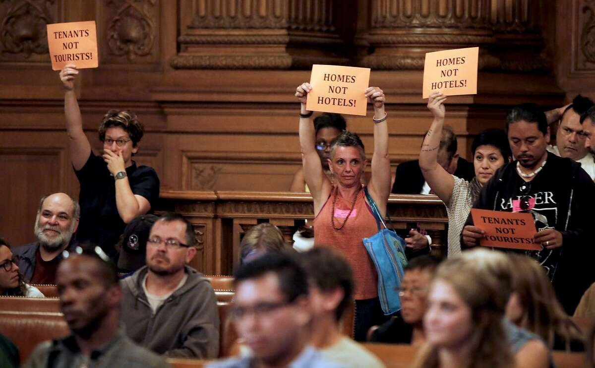 A few audience members hold signs after the vote, as the San Francisco Board of Supervisors voted to pass the ordinance sponsored by Supervisor Mark Farrell and Mayor Ed Lee to regulate Airbnb and other short term rental services in San Francisco, Calif., on Tues. July 14, 2015.