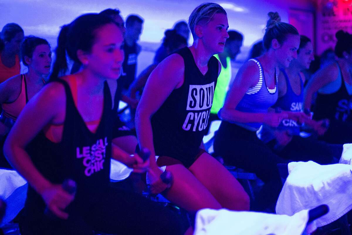Kimberly Radich, center, uses dumbbells while riding a station bike during a spin class at SoulCycle Castro in San Francisco, Calif. on Friday, July 10, 2015.