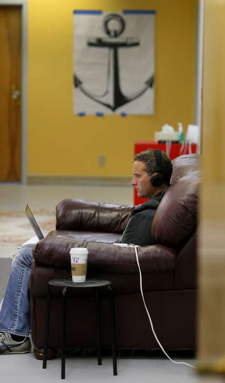 Brian Gannon works at the Anchor space at 1540 Market Street in a large comfortable sofa Tuesday July 14, 2015. Two buildings and a parking lot near the corner of Van Ness and Market Streets in San Francisco, Calif. may have a date with the wrecking ball, but before they are knocked down it is coming alive as a home for nonprofits and artists. Photo: Brant Ward, The Chronicle