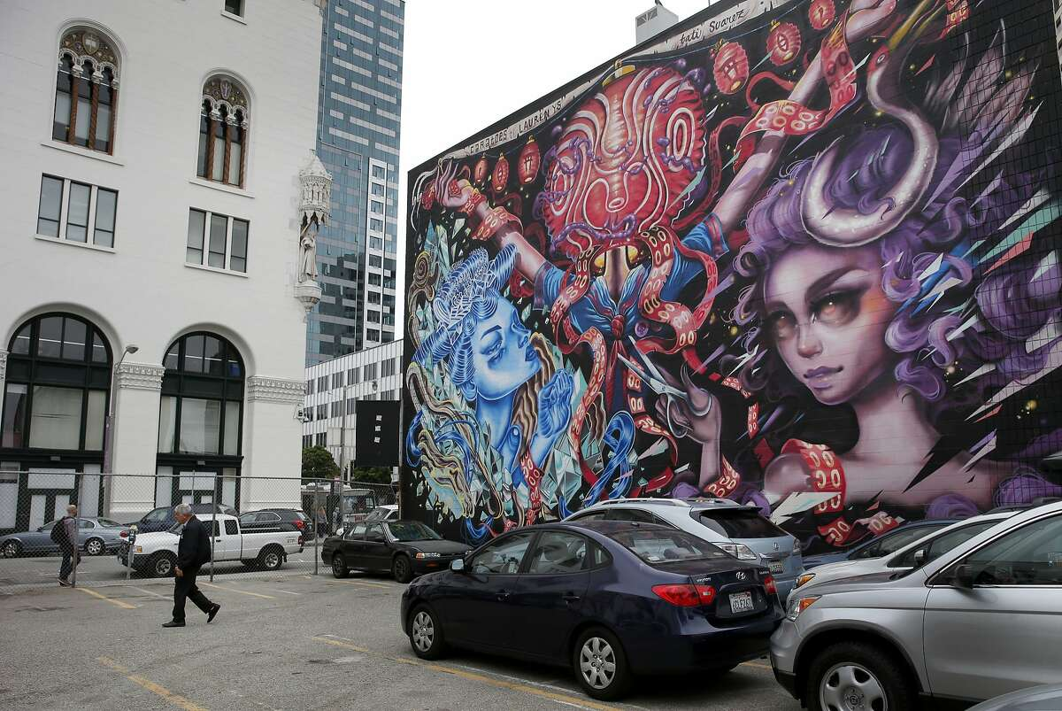 A view of the parking lot and the corner building with a mural Tuesday July 14, 2015. The corner building will soon house some social workers. Two buildings and a parking lot near the corner of Van Ness and Market Streets in San Francisco, Calif. may have a date with the wrecking ball, but before they are knocked down it is coming alive as a home for nonprofits and artists.