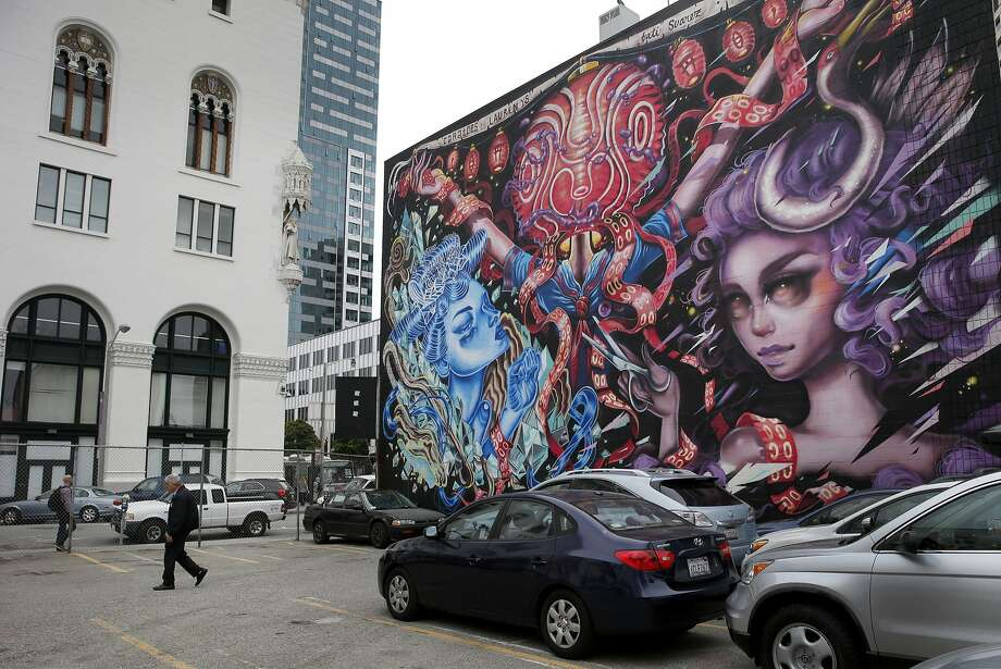 A view of the parking lot and the corner building with a mural Tuesday July 14, 2015. The corner building will soon house some social workers.  Two buildings and a parking lot near the corner of Van Ness and Market Streets in San Francisco, Calif. may have a date with the wrecking ball, but before they are knocked down it is coming alive as a home for nonprofits and artists. Photo: Brant Ward, The Chronicle